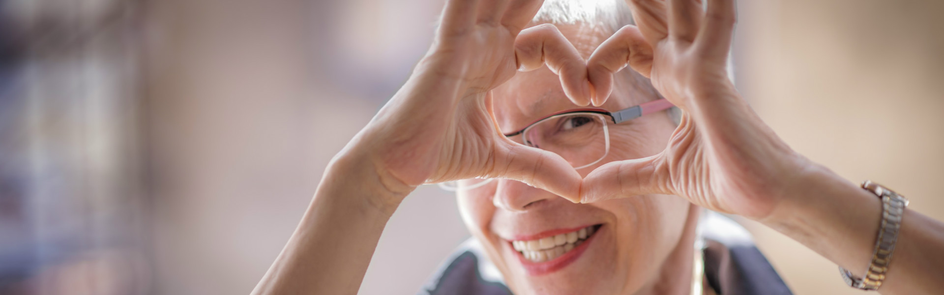 Woman smiling and making the shape of a heart with her 2 hands.