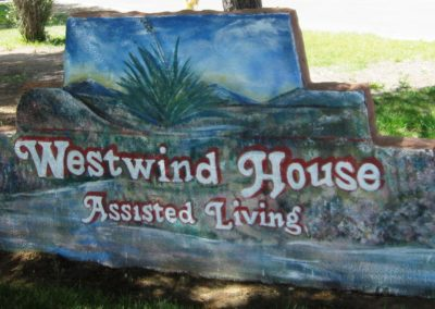 "Sign from Westwind House that reads ""Assisted Living"" and is painted on a rock."